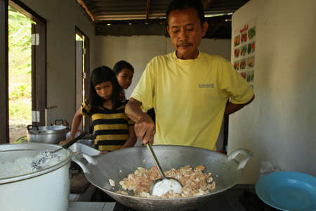 KO CHANG, THAILAND - JANUARY 6: Teacher prepares a meal for unknown children at school by project Cambodian Kids Care to help deprived children in deprived areas, on January 6, 2012 on Ko Chang, Thailand.