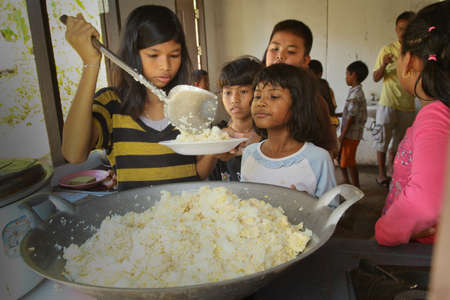 KO CHANG, THAILAND - JANUARY 6: Unknown children get food at lunch time at school by project Cambodian Kids Care to help deprived children in deprived areas, on January 6, 2012 on Ko Chang, Thailand.