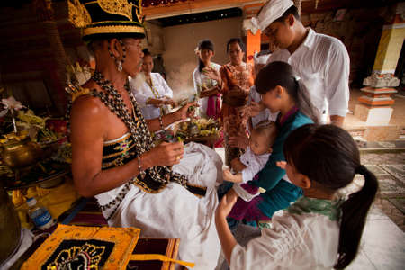 BALI, INDONESIA - MARCH 28: Hindu Brahmin during the ceremonies of Oton - is the first ceremony for baby's on which the infant is allowed to touch the ground on March 28, 2012 on Bali, Indonesia. Stock Photo - 12925641