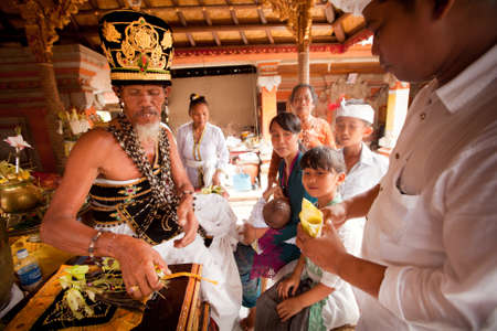 BALI, INDONESIA - MARCH 28: Hindu Brahmin during the ceremonies of Oton - is the first ceremony for baby's on which the infant is allowed to touch the ground on March 28, 2012 on Bali, Indonesia. Stock Photo - 12925636