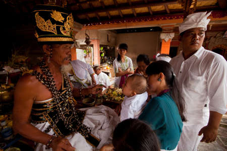 BALI, INDONESIA - MARCH 28: Hindu Brahmin during the ceremonies of Oton - is the first ceremony for baby on which the infant is allowed to touch the ground on March 28, 2012 on Bali, Indonesia. Stock Photo - 12935972