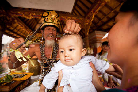 BALI, INDONESIA - MARCH 28: Unidentified child during the ceremonies of Oton - is the first ceremony for baby on which the infant is allowed to touch the ground on March 28, 2012 on Bali, Indonesia. Stock Photo - 13096085
