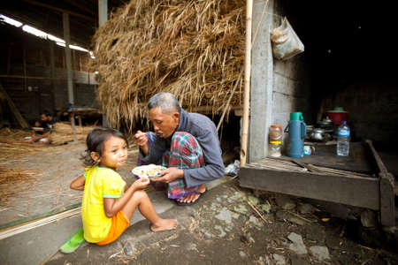 BALI, INDONESIA - APRIL 3: Unidentified poor child eats with his father during a break working on the farm  on April 3, 2012 on Bali, Indonesia. Daily caloric intake per capita in Indonesia is 2891 kcal per person.