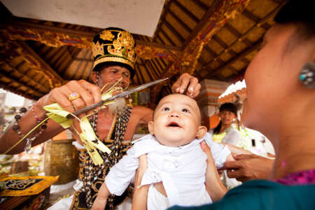 BALI, INDONESIA - MARCH 28: Unidentified child during the ceremonies of Oton - is the first ceremony for baby on which the infant is allowed to touch the ground on March 28, 2012 on Bali, Indonesia. Stock Photo - 13154565