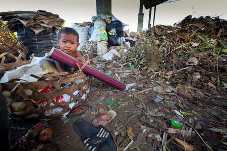 BALI, INDONESIA - APRIL 11: Unidentified child is sitting in a landfill during his parents are working in a scavenging at the dump on April 11, 2012 on Bali, Indonesia. Bali daily produced 10,000 cubic meters of waste.
