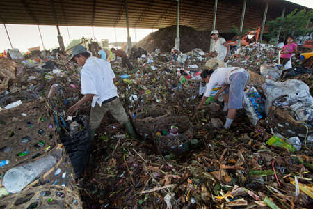 BALI, INDONESIA - APRIL 11: Poor people from Java island working in a scavenging at the dump on April 11, 2012 on Bali, Indonesia. Bali daily produced 10,000 cubic meters of waste. Stock Photo - 13266621