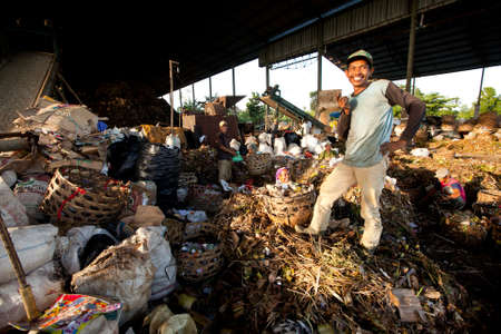 BALI, INDONESIA - APRIL 11: Poor people from Java island working in a scavenging at the dump on April 11, 2012 on Bali, Indonesia. Bali daily produced 10,000 cubic meters of waste. Stock Photo - 13337322