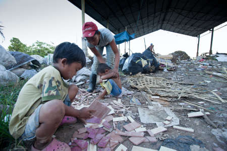 BALI, INDONESIA - APRIL 11: Unidentified children is sitting during his parents are working in a scavenging at the dump on April 11, 2012 on Bali. Bali daily produced 10,000 cubic meters of waste.