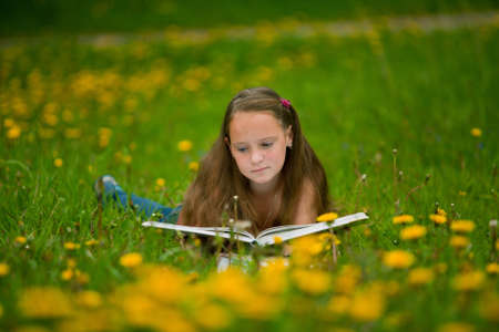 A girl 11 years old reads a book in the meadow photo