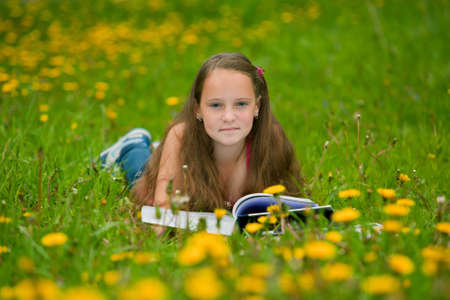 11 years: A girl 11 years old reads a book in the meadow Stock Photo