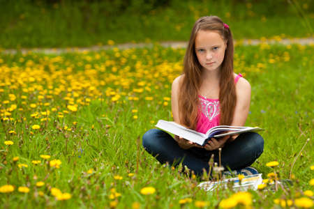 11 years old: A girl 11 years old reads a book in the meadow Stock Photo
