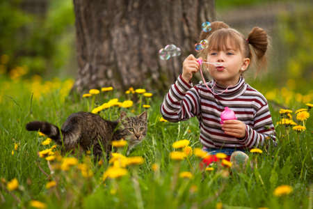 Portrait of funny lovely little girl and a cat, blowing soap bubbles photo