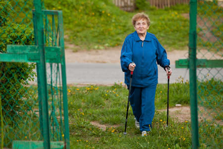 Active old woman  85 years old  nordic walking outdoors  photo