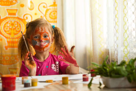 Beautiful little girl artist with paint of face. photo