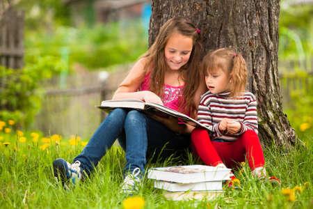 Children reading the book in summer park photo