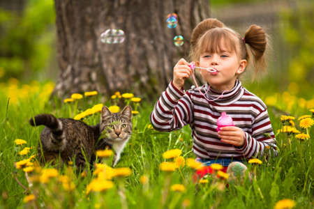 Funny lovely little girl and a cat, blowing soap bubbles photo