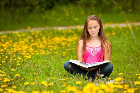 Girl (looking at the camera) reads a book in the meadow  photo