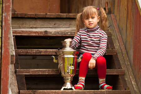 Funny lovely little girl posing sitting near the Russian Samovar on the porch of the farmhouse. photo