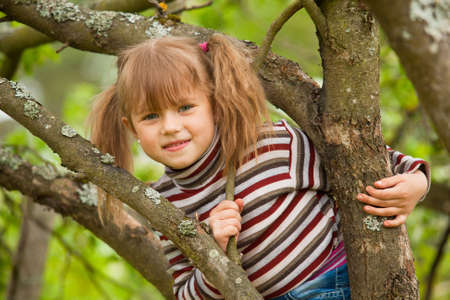 Funny lovely little girl posing sitting on a tree in the garden photo