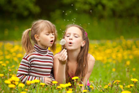 Little sisters blowing dandelion seeds away in the meadow photo