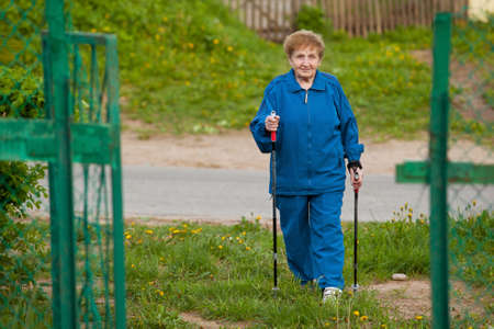 action fund: Active old woman nordic walking outdoors (85 years old) .