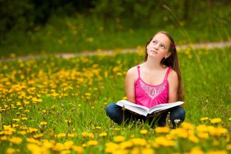 La niña se sienta en una hierba y sueños mientras lee un libro