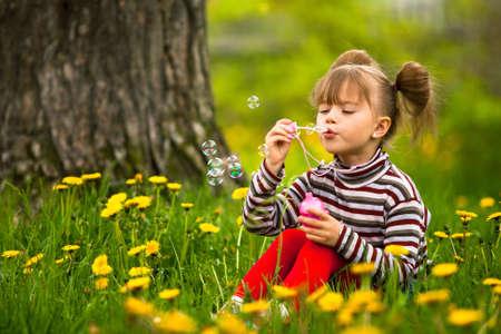 burbujas jabon: Encantador y pequeño de cinco años chica soplando burbujas de jabón en el parque