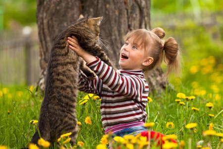 Bir kedi ile oynarken komik sevimli küçük kız Stock Photo