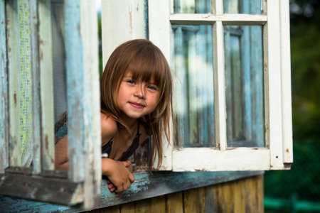 Beautiful little girl looks out the window rural house photo