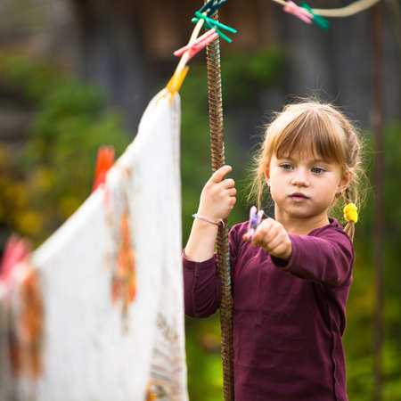 Funny lovely little five-year girl with clothespin outdoor photo