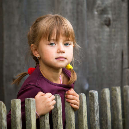 Beautiful child standing near vintage rural fence   square format  photo