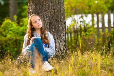 cute teen girl: Красивая подростков девушка-писать в записной книжке, сидя в парке мечтательно смотрит вверх Фото со стока