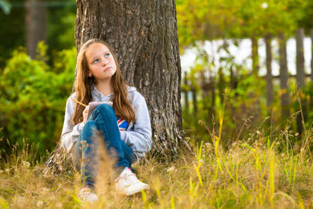 girl notebook: Beautiful teen-girl writing in a notebook while sitting in the park  dreamily looks up