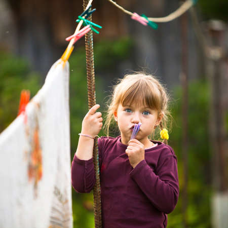 Sweet funny girl with clothespin and the clothesline  photo