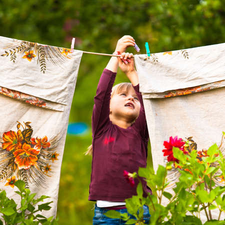 Sweet  five-year girl with clothespin and the clothesline photo