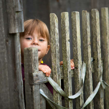 Beautiful child standing near vintage rural fence   square Stock Photo - 15071195