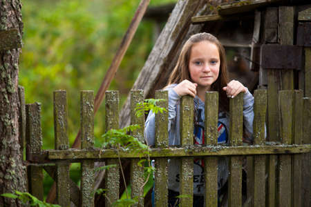 Teen-girl standing near vintage rural fence  Stock Photo - 15071205