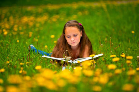 Child reading a book while lying in the grass Stock Photo