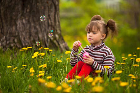 Funny lovely little five-year girl blowing soap bubbles in the park photo