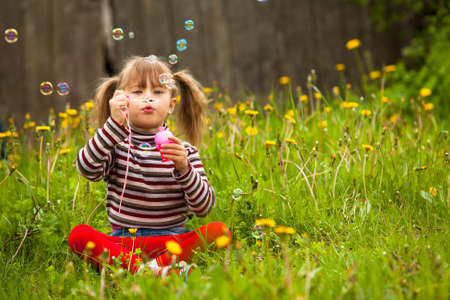 blowing bubbles: Five-year girl blowing soap bubbles in the park Stock Photo