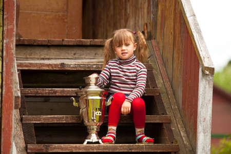 barn girls: Lovely little girl posing sitting near the Russian Samovar on the porch of the farmhouse.