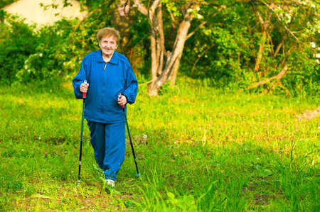 action fund: Active old woman (85 years old) nordic walking outdoors.
