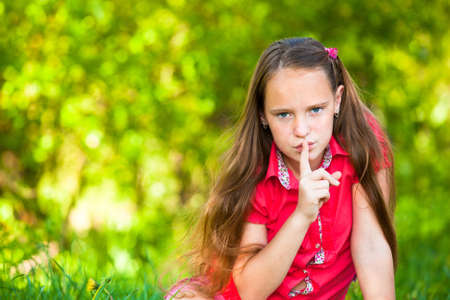 hushing: Young girl with her finger over her mouth, hushing.