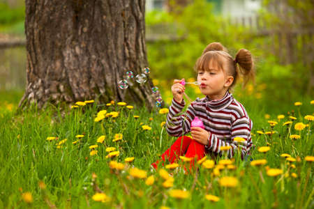 Beautiful funny lovely little five-year girl blowing soap bubbles in the park photo