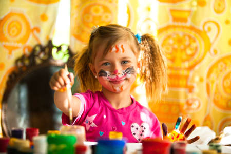 Beautiful little girl artist with paint of face photo