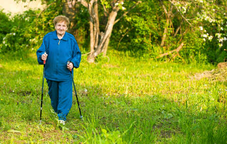 action fund: Active woman  85 years old  nordic walking outdoors