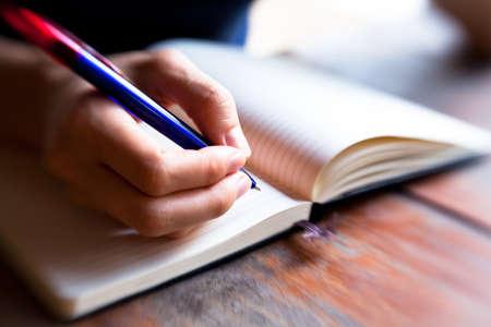 Close-up van de hand pen schrijft in een notebook wazig