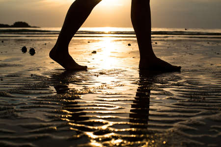 Feet of a young woman walking on the beach at sunset  backlit