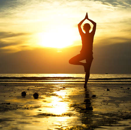 Silhouette of a beautiful yoga woman in the evening Stock Photo