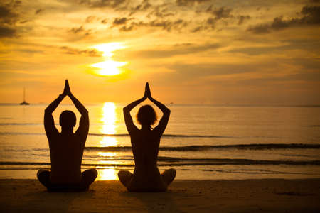 beach yoga: Young couple practicing yoga on the sea beach at sunset